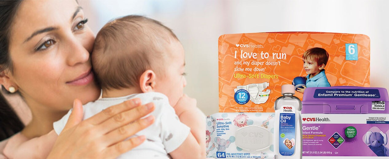 Mother holding her baby and smiling. CVS Health product packages of Ultra Soft Diapers, Ultra Soft Sensitive baby wipes, Baby Oil and Gentle Infant Formula with iron.