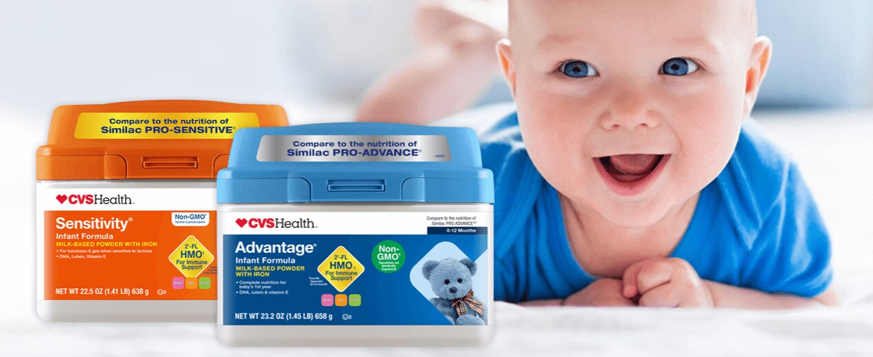 Product packages of CVS Health Sensitivity Infant Formula with HMO and CVS Health Advantage Infant Formula with HMO. Smiling baby boy.