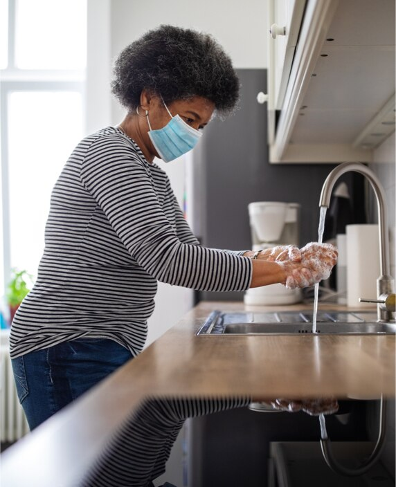 An image of woman in face covering washing her hands in a kitchen